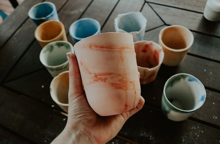 a hand holding a coloured pot