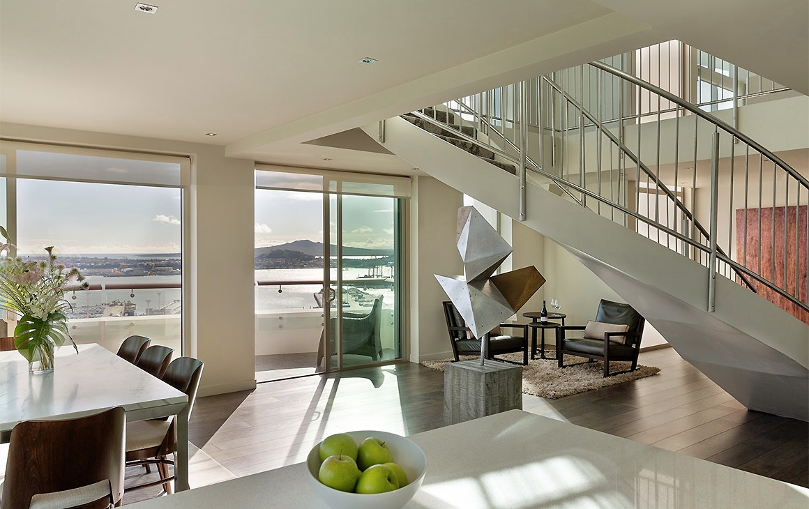 The penthouse suite at the Pullman Auckland shows a spacious room with views of Rangitoto in the background.