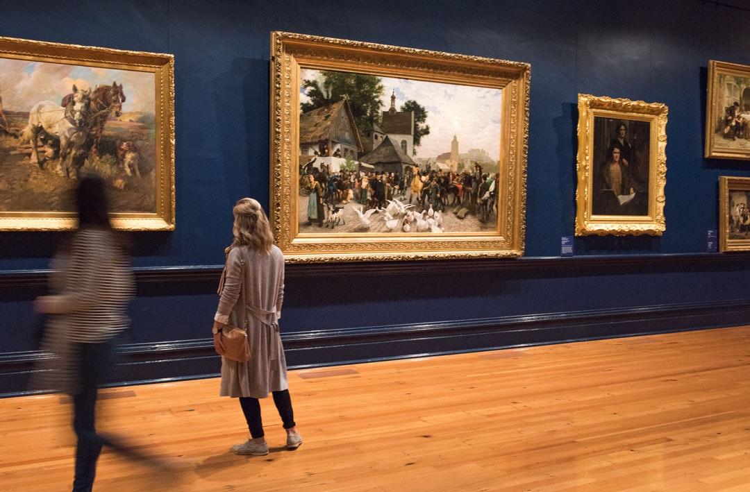 Visitors look at framed paintings on the wall at Bendigo Art Gallery.