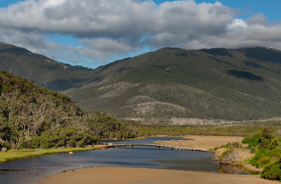 Tidal River in Wilsons Promontory National Park flows below the mountains above. A bridge across the river can be seen in the distance.
