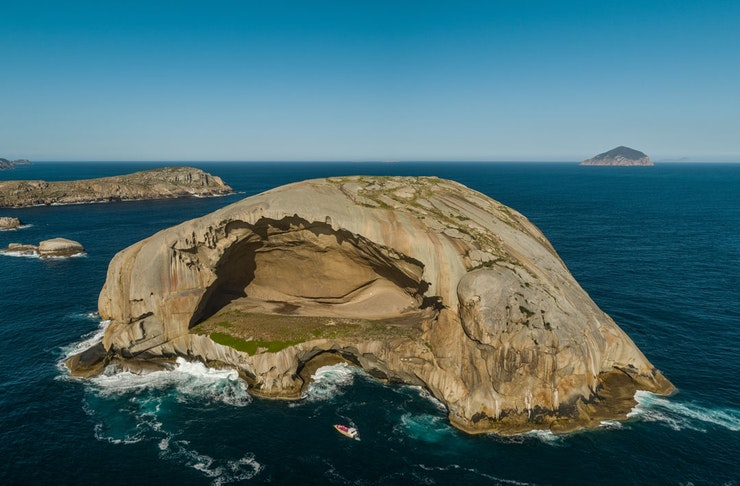 Skull Rock off the south coast of Victoria. A tourist boat is in the foreground in rough seas.