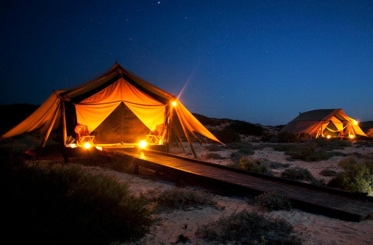 Two tents on sandy dunes are lit up at night.