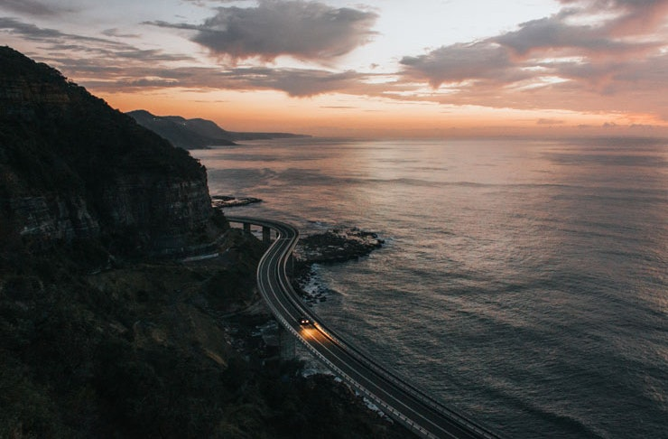 A single car travels down along Seacliff Bridge south of Sydney at dusk.