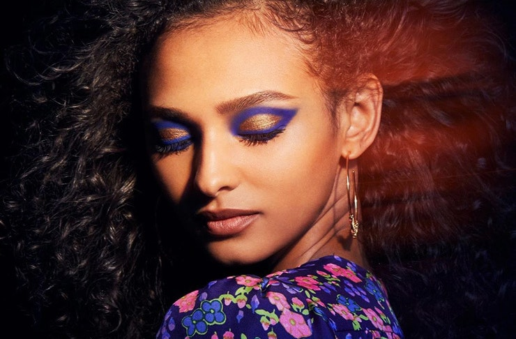 A woman with purple-blue eye makeup from the Marc Jacobs Beauty range.
