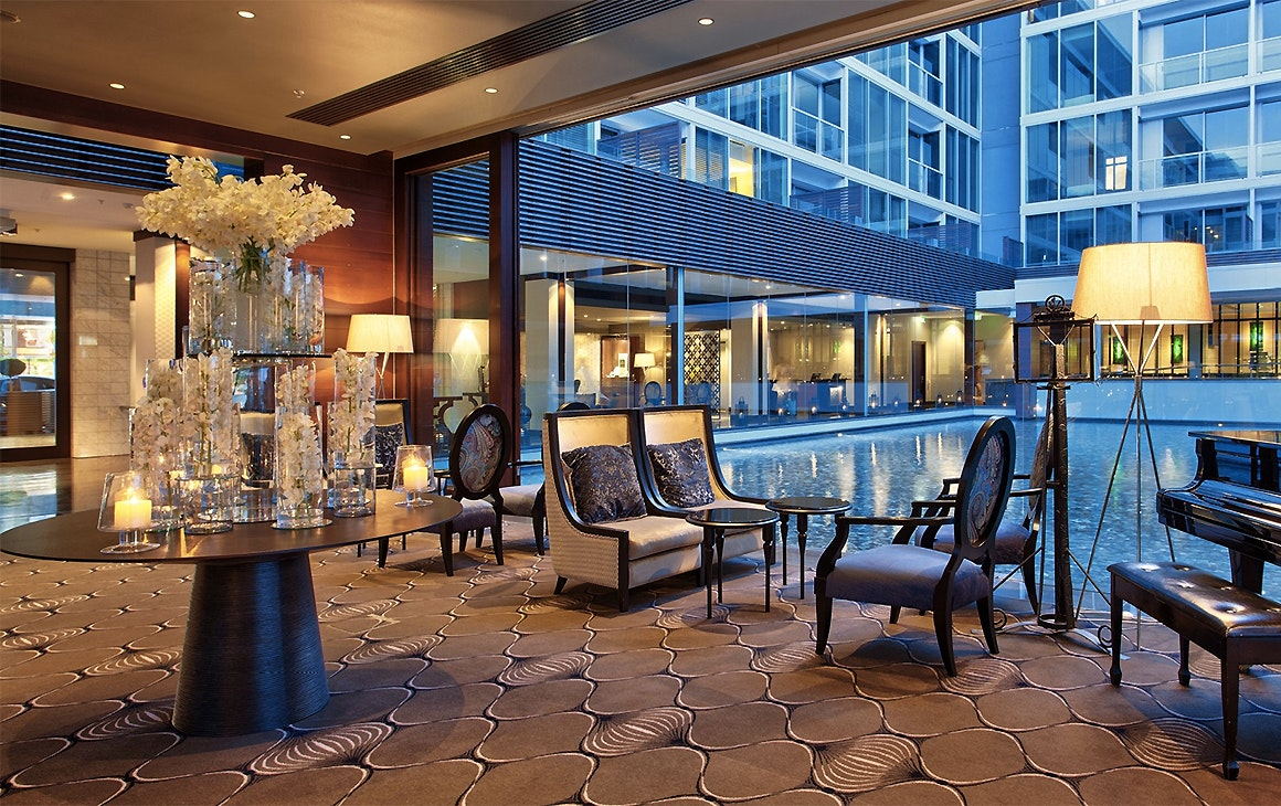 A view of the opulent lobby at the Sofitel Hotel in the Viaduct harbour showing chairs looking out over the pool.