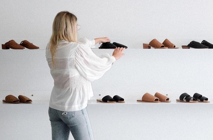 Woman growing St. Agni shoes on white shelves.