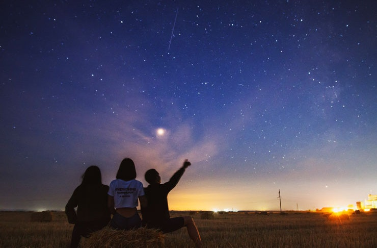 A group of three people stargazing in regional NSW.