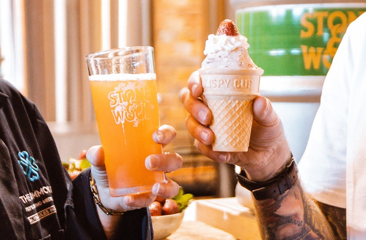 A beer pint and a strawberry ice cream being held by two people