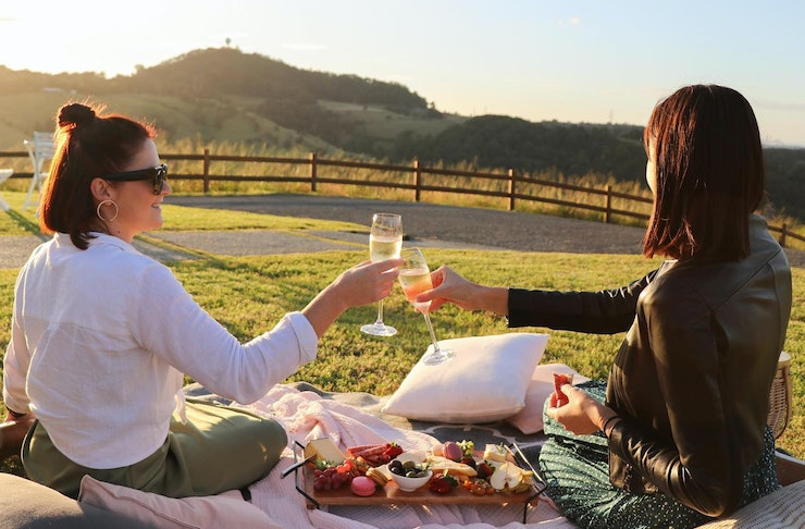 Two young women cheers their drinks on a picnic rug, overlooking the Tweed hinterland. There is a picnic spread between the,