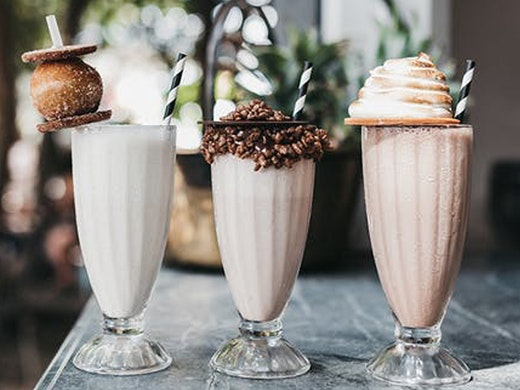 Three milkshakes with crazy toppings line up on a table.