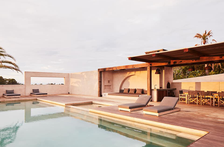 A spanish style pool surrounded by tan coloured concrete and outdoor furnishings.