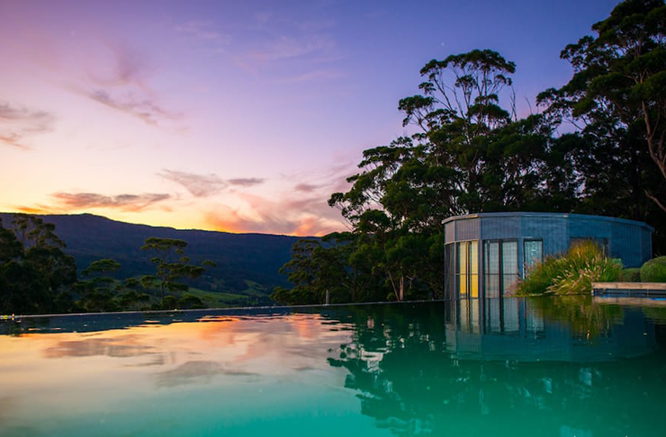 An infinity pool over looking a lush green hillside in the evening sun.