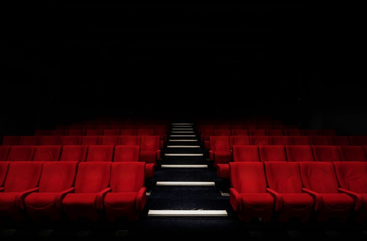 An empty theatre with rows of red velvet chairs.