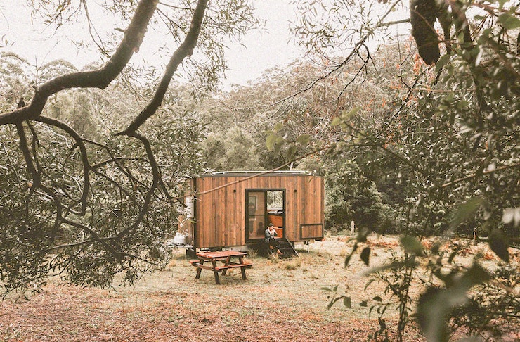 A tiny houses made of mostly timber sitting in the middle of a paddock surrounded by trees. A male is sitting on the step having a coffee.