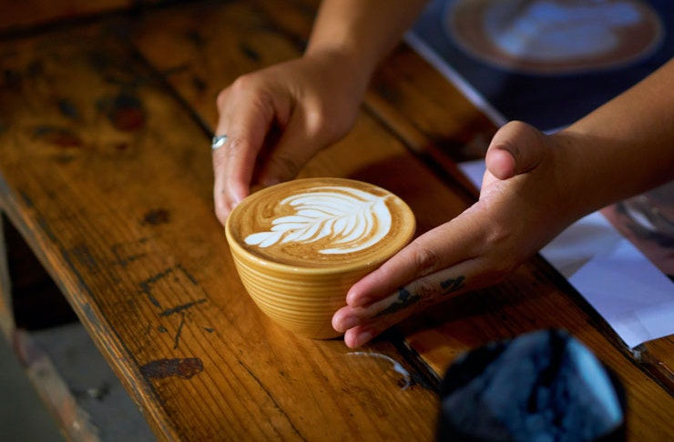 A latte being presented on a wooden table.