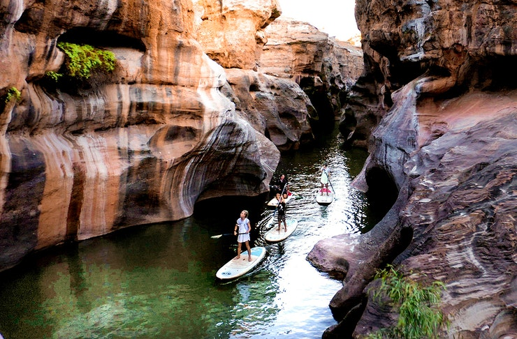 Several people SUP through a deep gorge