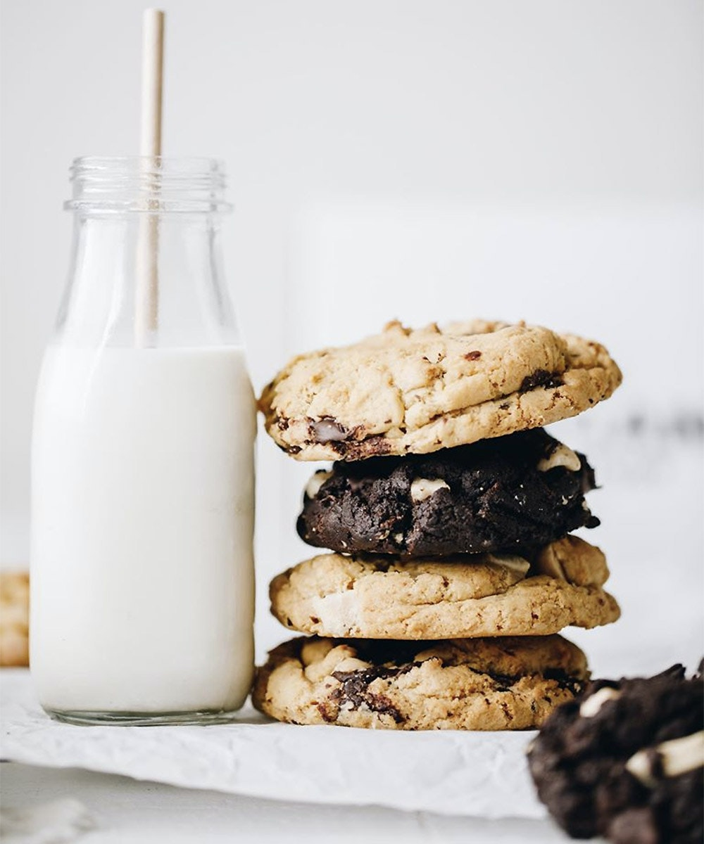 Four thick vegan cookies stacked on top of each other next to a glass of plant-based milk from the Vegan Treatory.