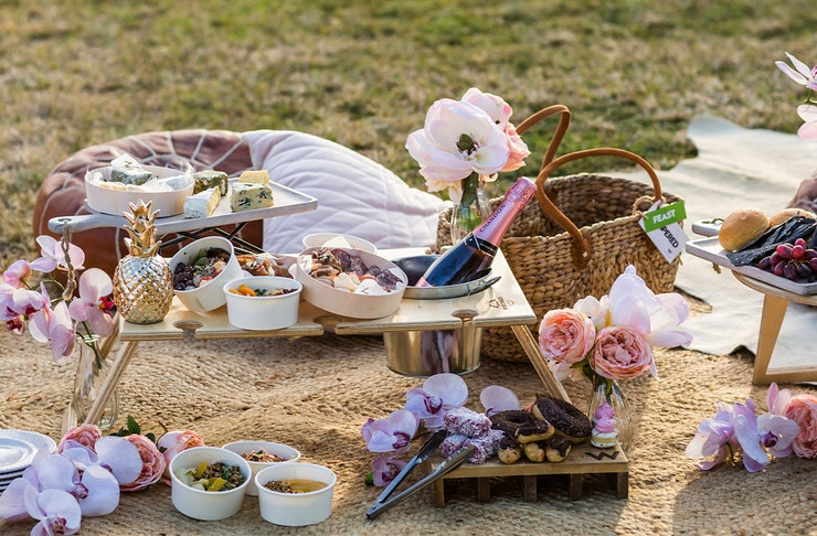 A display of food and beverages from a picnic hamper on a blanket over the grass