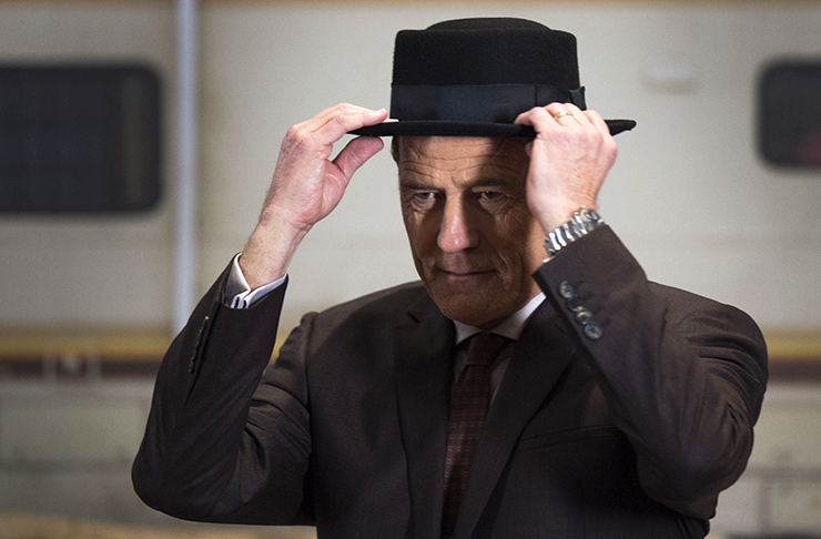 Bryan Cranston playing Walter White from Breaking Bad, wearing a suit and tipping his black cap.