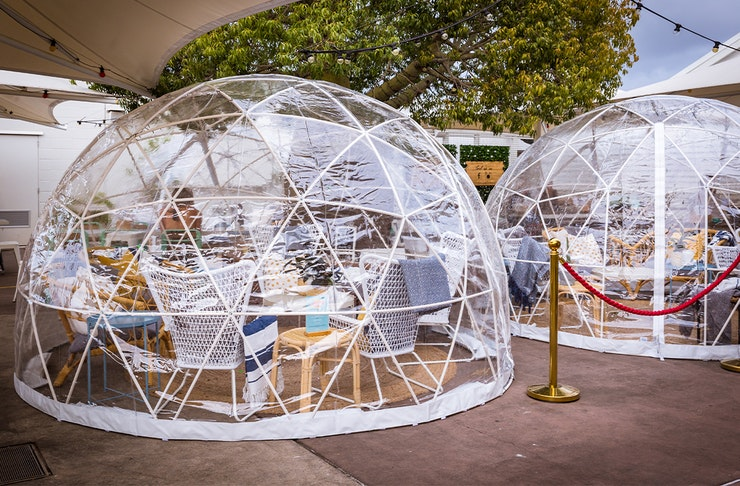 Two clear igloos with tables inside