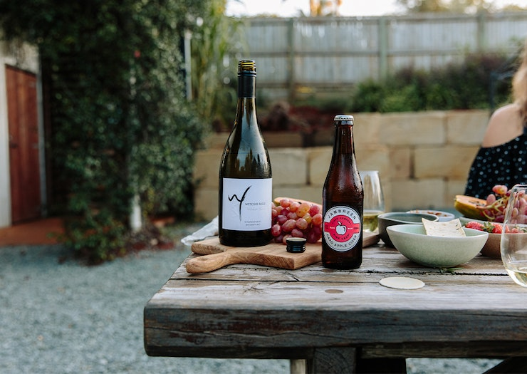 A bottle of wine and cider on a table with plates and boards