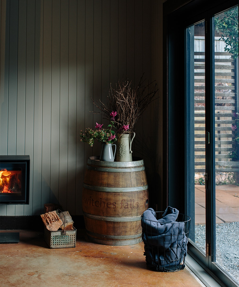 inside of winery bar, with a fireplace and barrel with flowers on top in a watering can