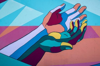 a set of multi-coloured hands is painted on a wall.