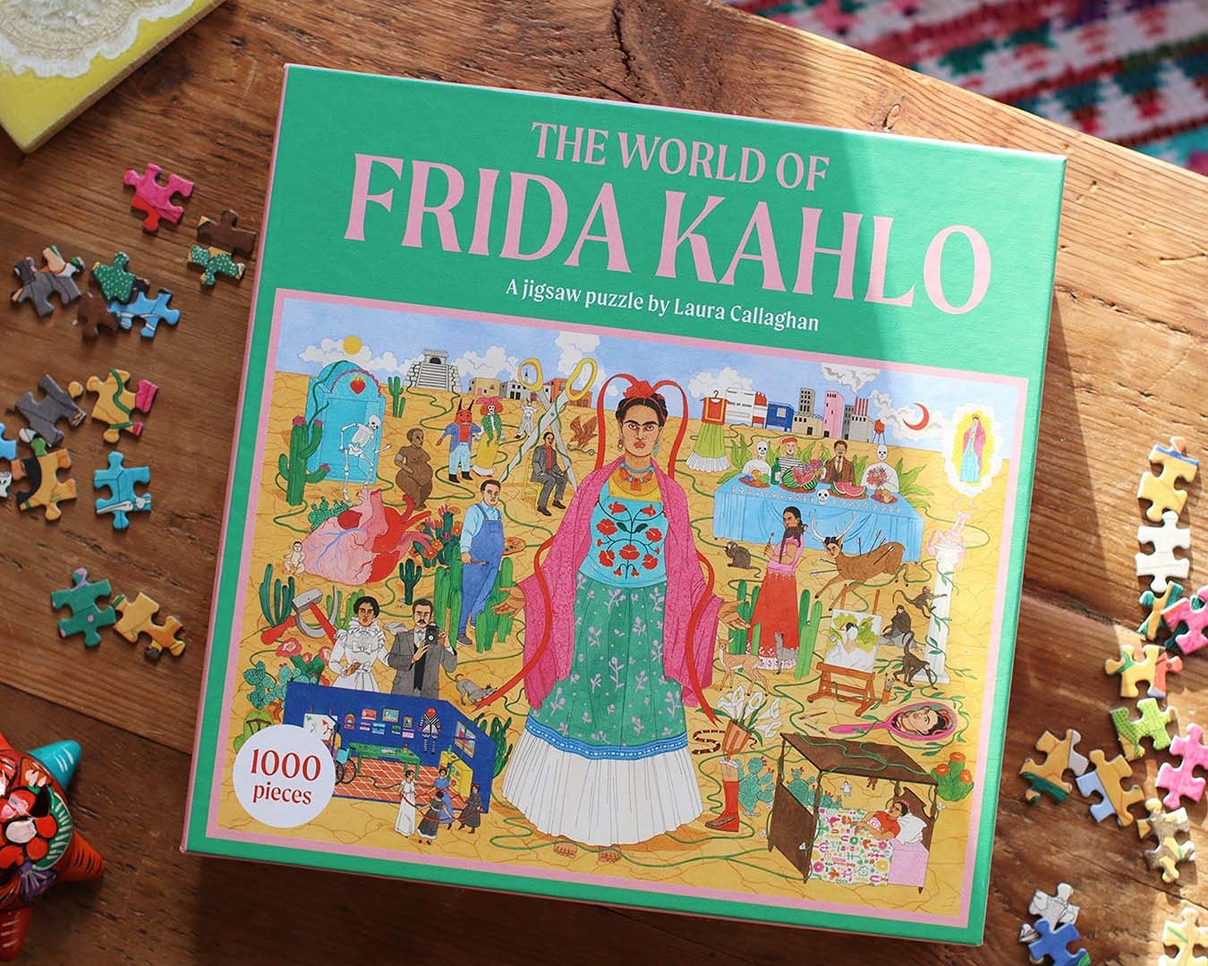A puzzle box, featuring an illustration of Frida Kahlo, sits on wooden table with a few pieces scattered around.