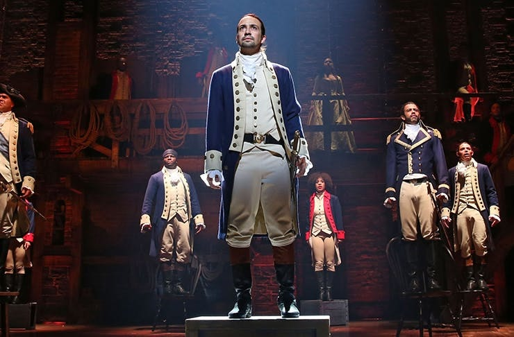 The character of Alexander Hamilton stands in the middle of the stage, with co-stars scattered around him.