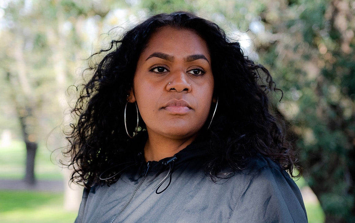 Close up shot of Miiesha, wearing a black jacket and hoop earrings, looking thoughtfully into the distance.