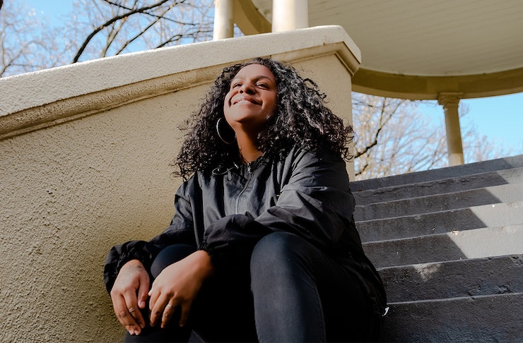 Miiesha dressed in all black, smiles while sitting on a set of stairs.