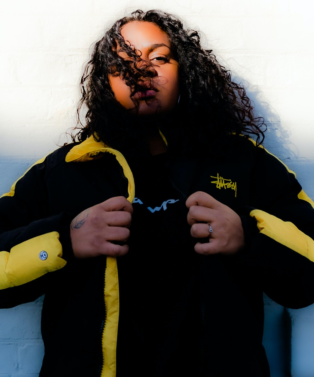 Miiesha, has some of her curls falling across her face, while holding on to the lapels of her black and yellow jacket.