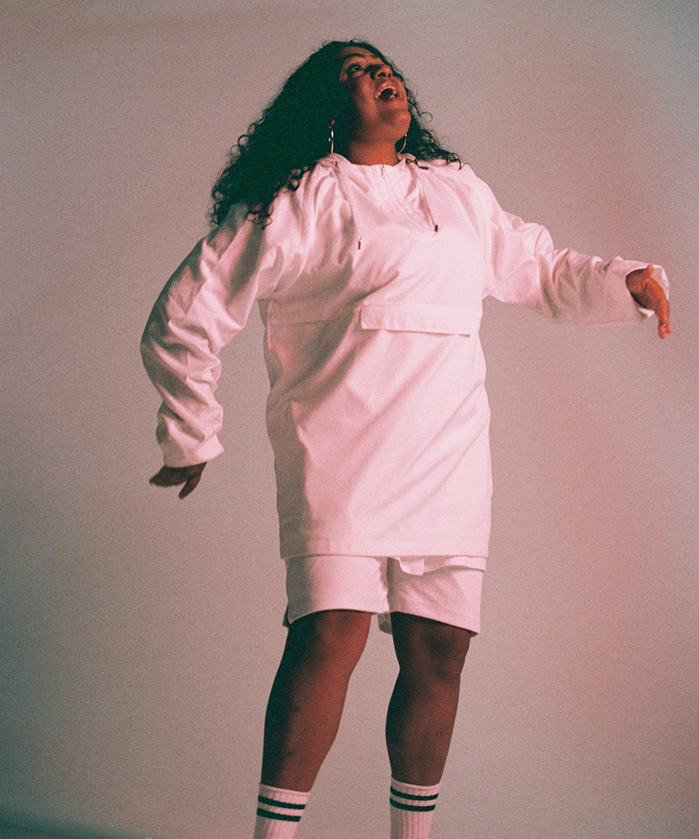 Miiesha, wearing a matching white jumper and shorts, jumps in the air.