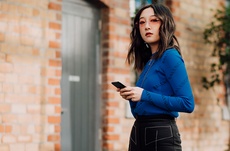 Style influencer Nicole Ku standing holding her Samsung Z Flip mobile phone in a blue sweater and black pants.