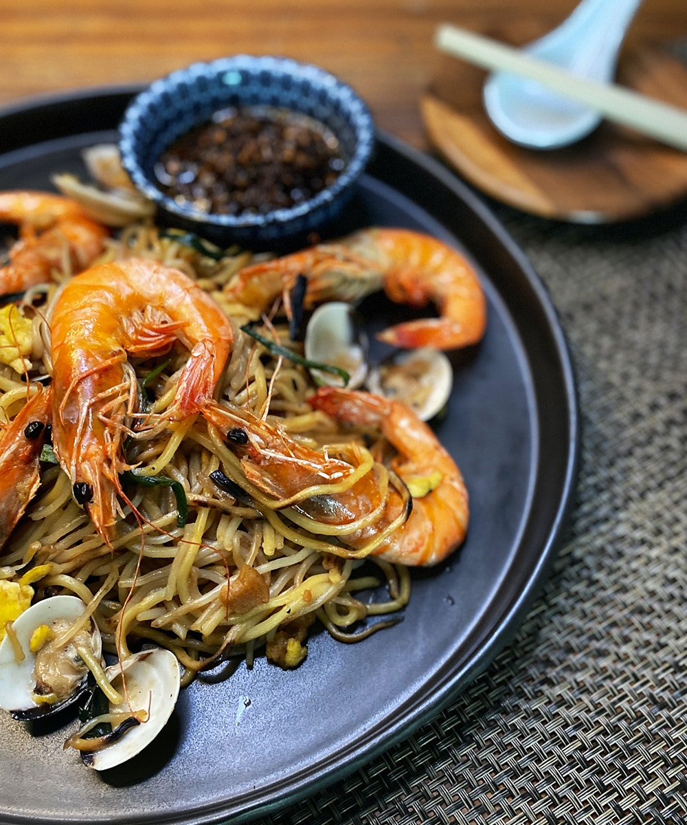 a plate with a drool-worthy pile of noodles and king prawns.