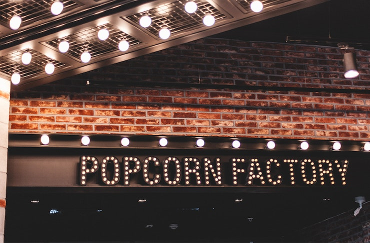 a neon sign reading popcorn factory hangs on the front of a brick building.