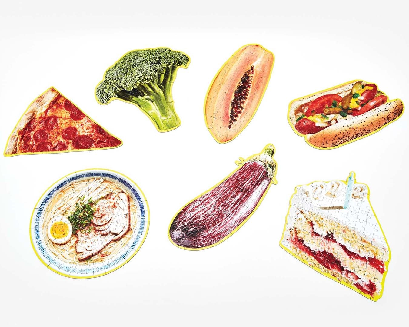 A selection of mini puzzles depicting a slice of pizza, hotdog, cake, ramen, melon, eggplant and broccoli.