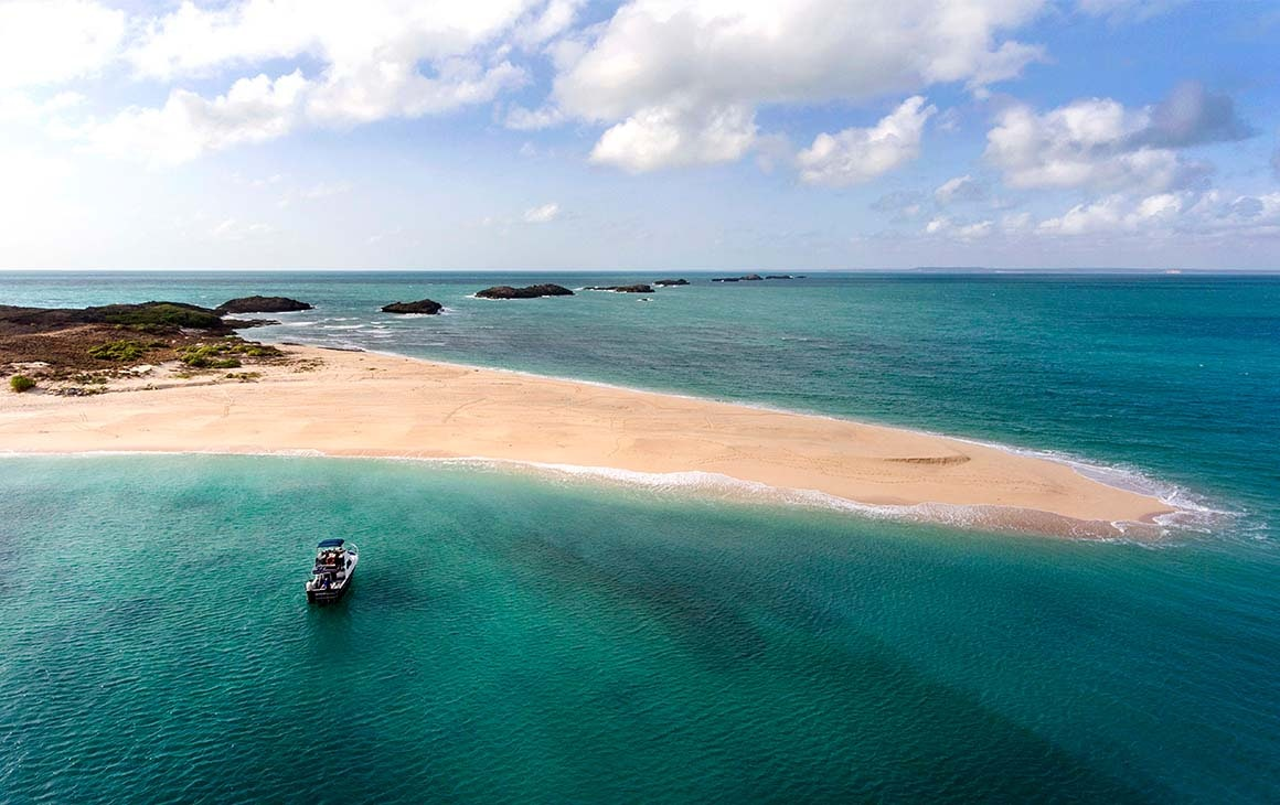 a stunning stretch of white sand, juts out into azure ocean.