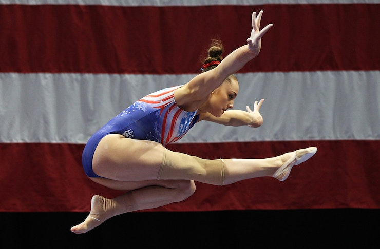 An American gymnast is captured mid-flip in the air. Behind her is a red and white flag.