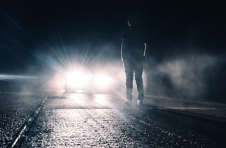 a figure stands in front of a car at night, illuminated by the lights.