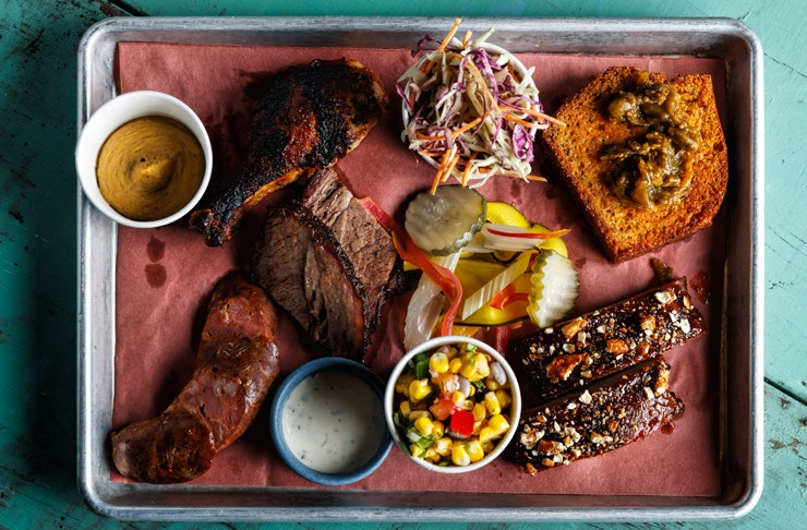 metal platter filled with juicy smoked meat, corn side, sold slaw and hickory sauce