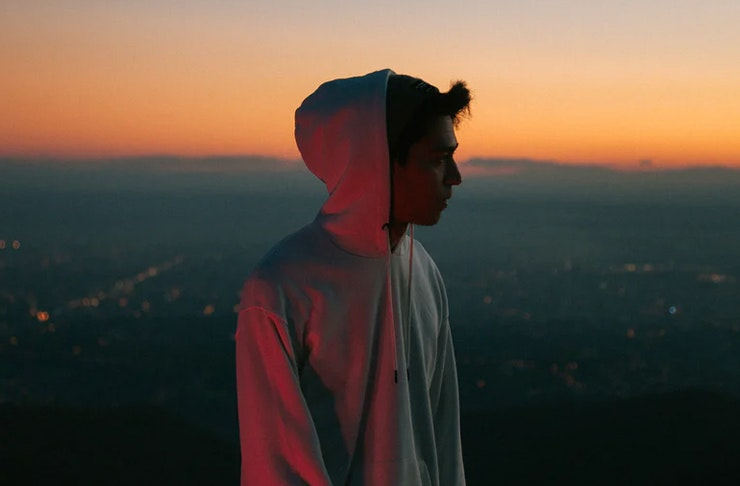 silhouette of young boy at sunset with hoodie on