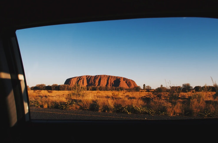 view of Uluru at sunset in Northern Territory from window of driving car