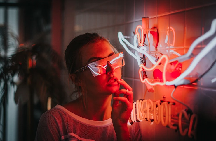 young woman wearing futuristic screen glasses leaning next to neon sign hanging on tiled wall