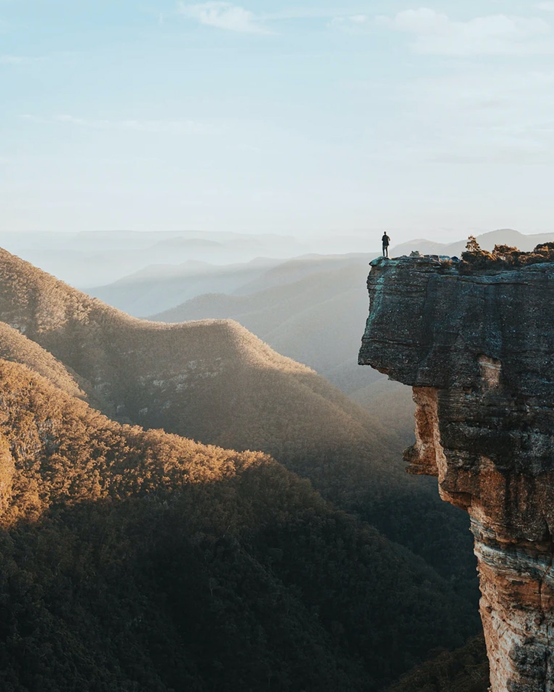 view from mountain in sydney's blue mountain ranges, man standing on edge of cliff