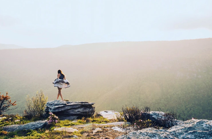 young woman walking along rocky cliff