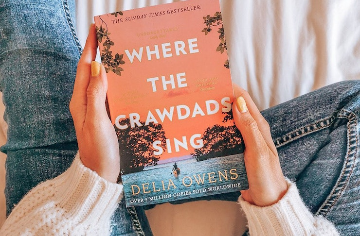 a woman holds a copy of Where The Crawdads Sing in her lap.