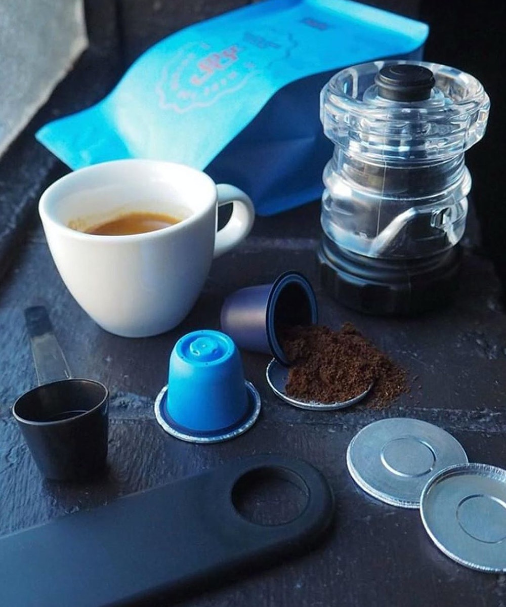 coffee pods and beans sit on a blue benchtop with a cup of coffee in front.
