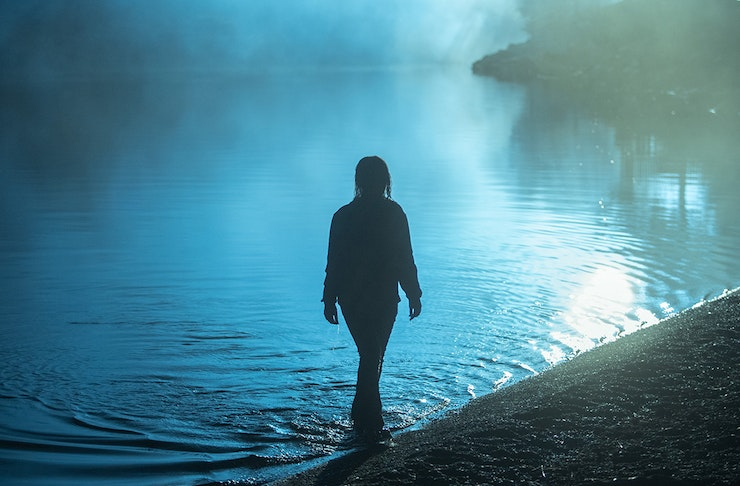 The shadowy figure of a woman emerges from a lake at night.