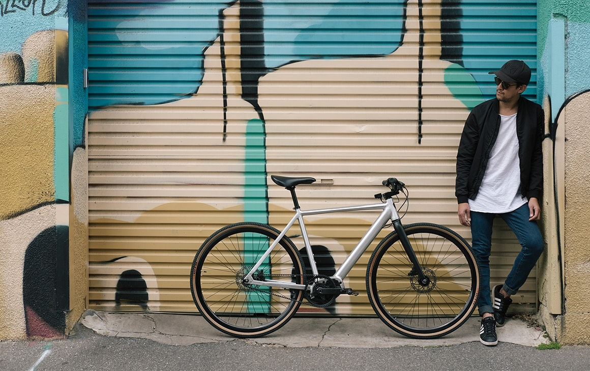 a man stands next to a bike in front of a colourful wall.